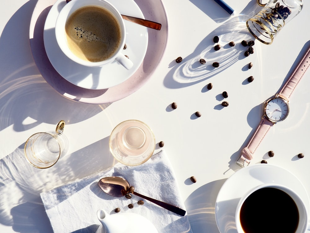 flat lay photography of teacup, saucer, watch, cup, and spoon