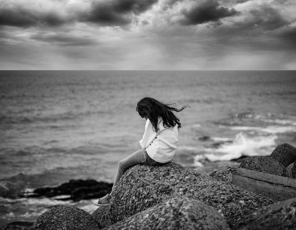 Grayscale Photography Of Woman Sitting Near Body Of Water Photo Free Rock Image On Unsplash