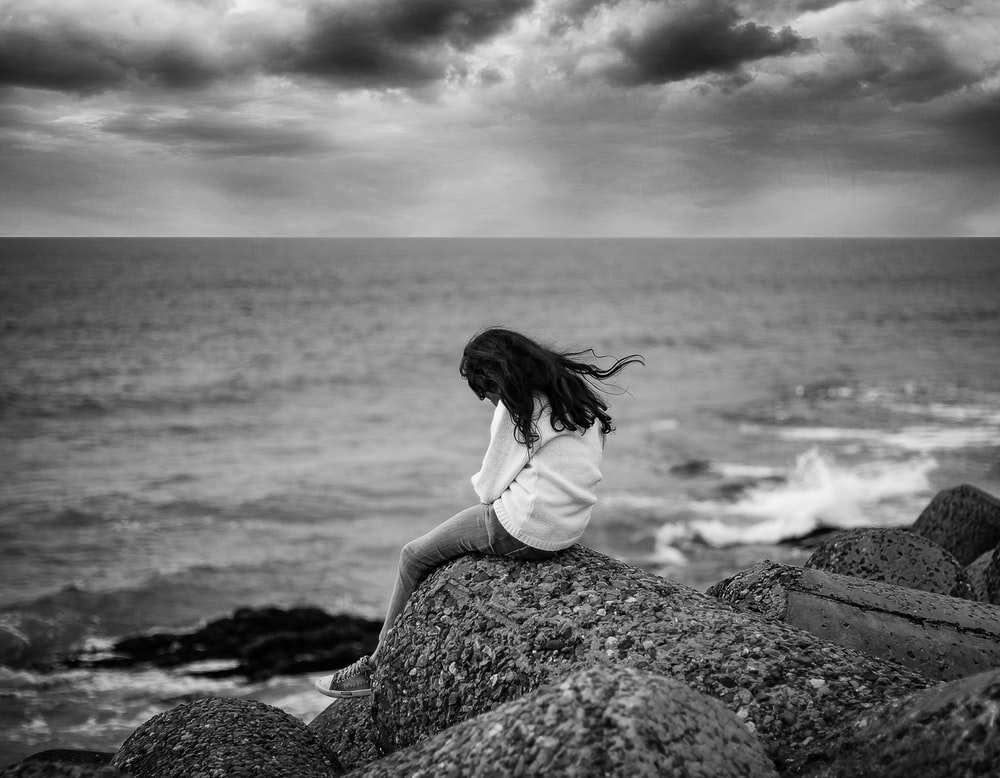 grayscale photography of woman sitting near body of water