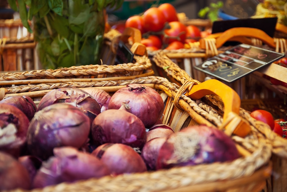 selective focus photography of onions in basket