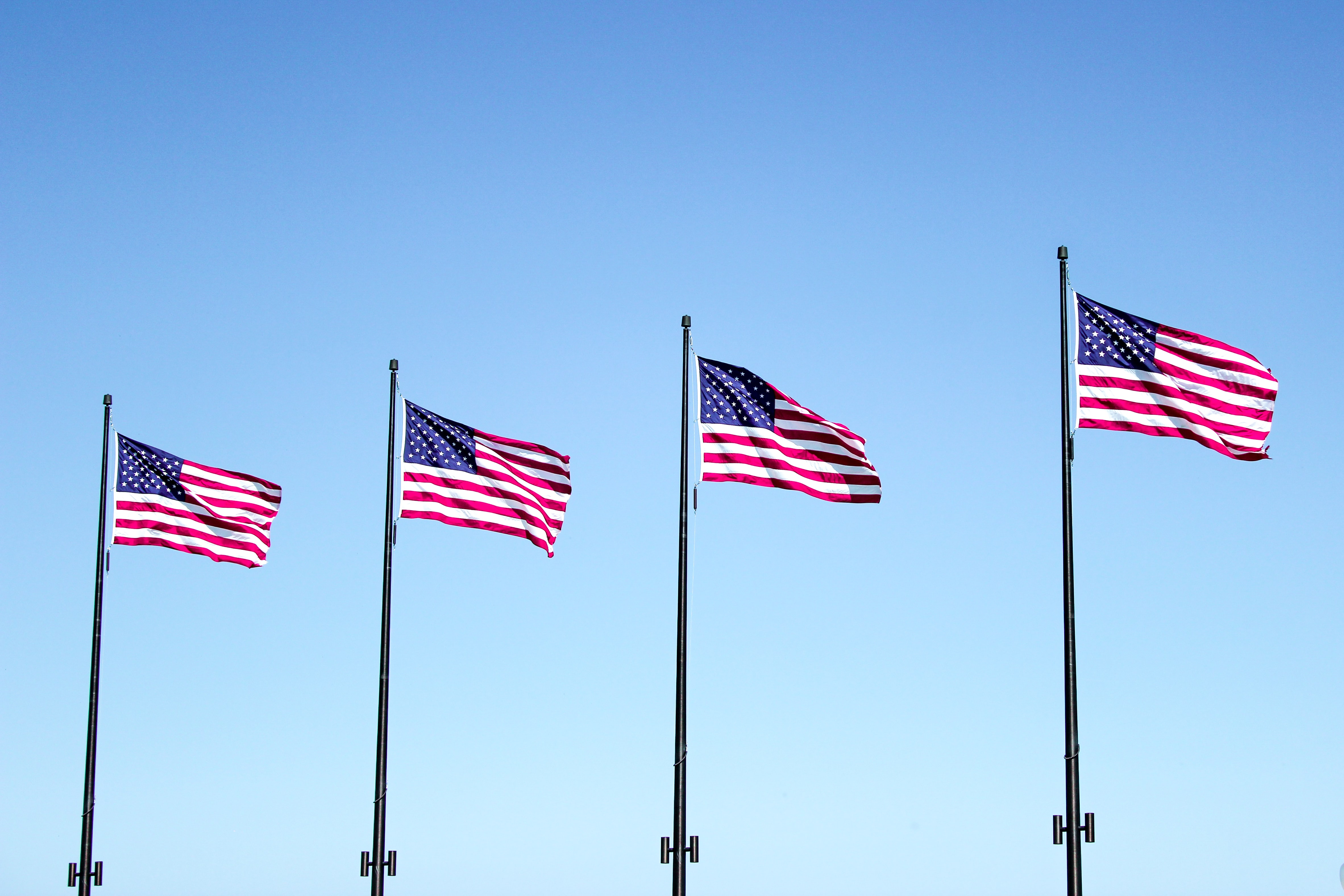 four USA flags under blue sky