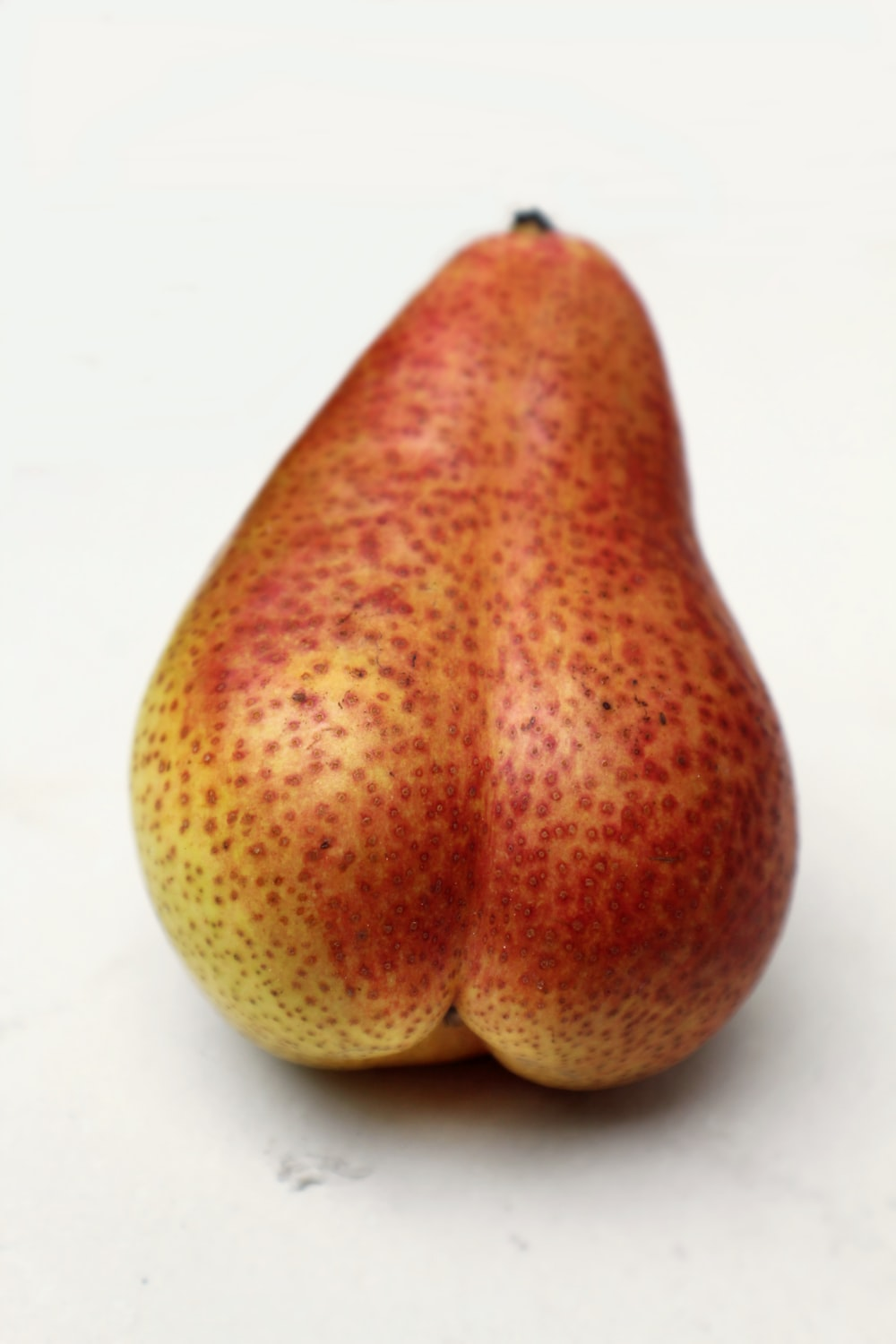 red and yellow pear on white surface