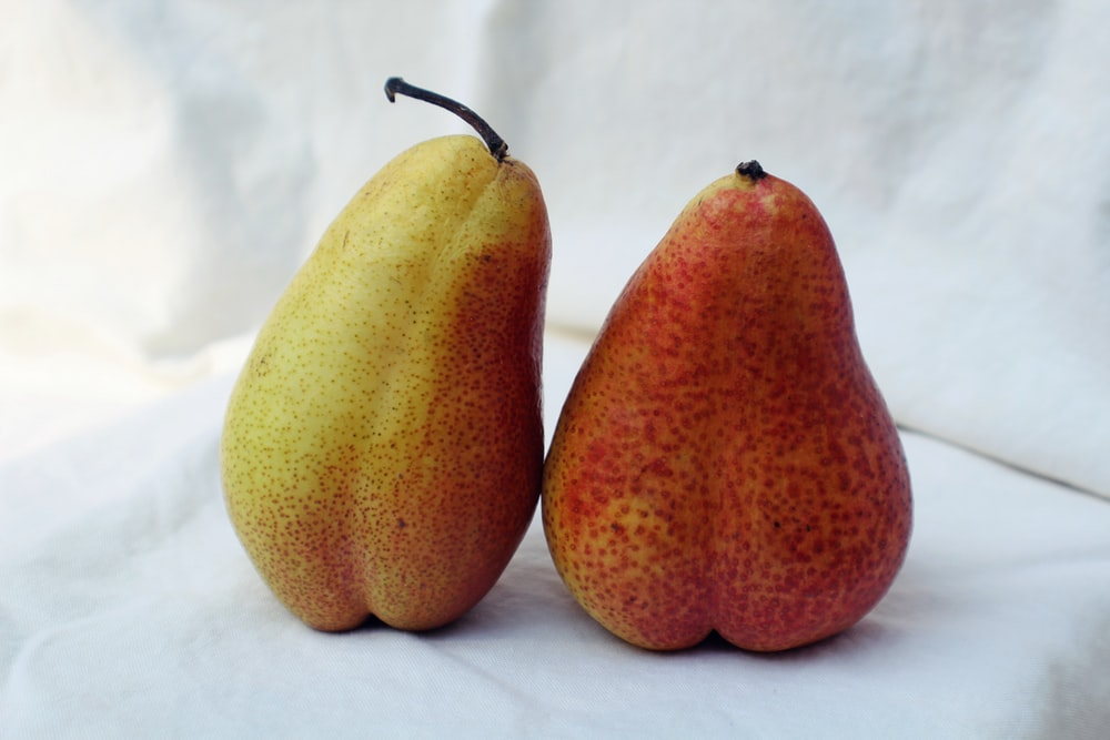 two yellow pears on white textile