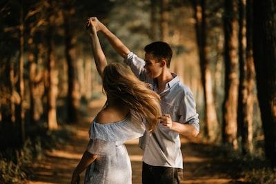 木々の中を笑顔で手を繋ぐ男女の様子