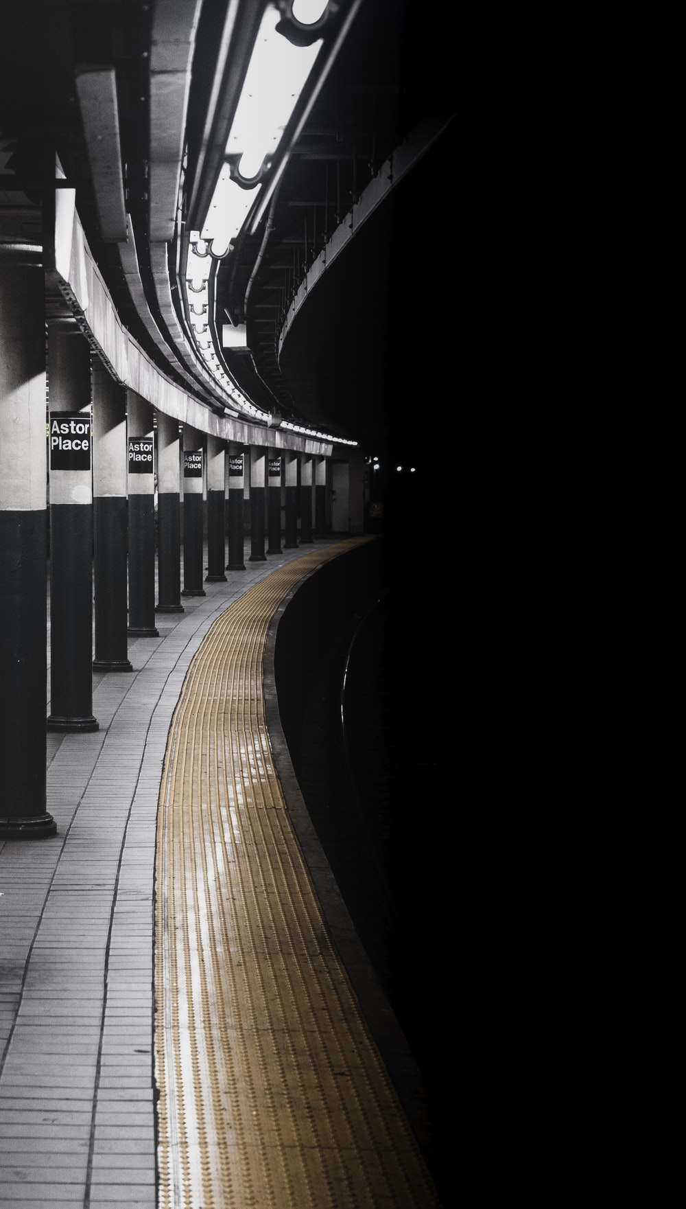 grayscale photo of train rail on tunnel
