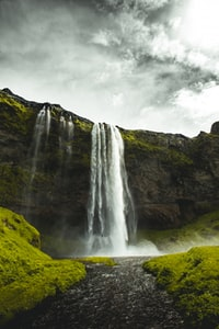 waterfalls under cloudy sky during daytime