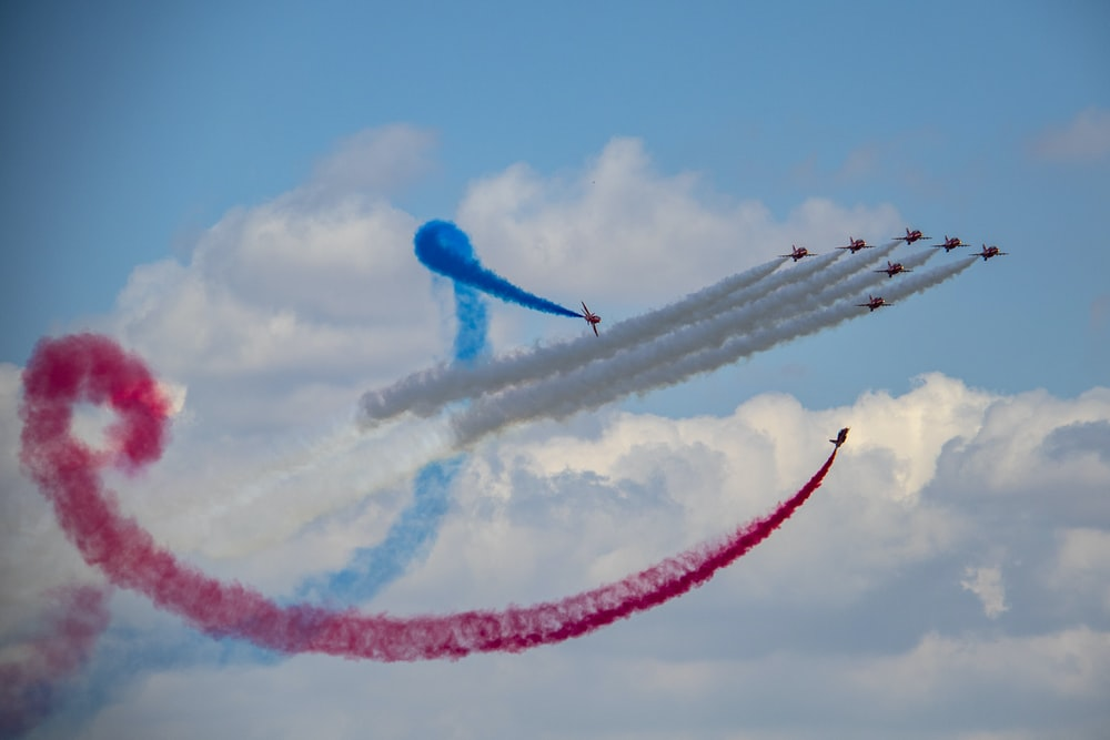 several fighter planes doing smoke exhibition