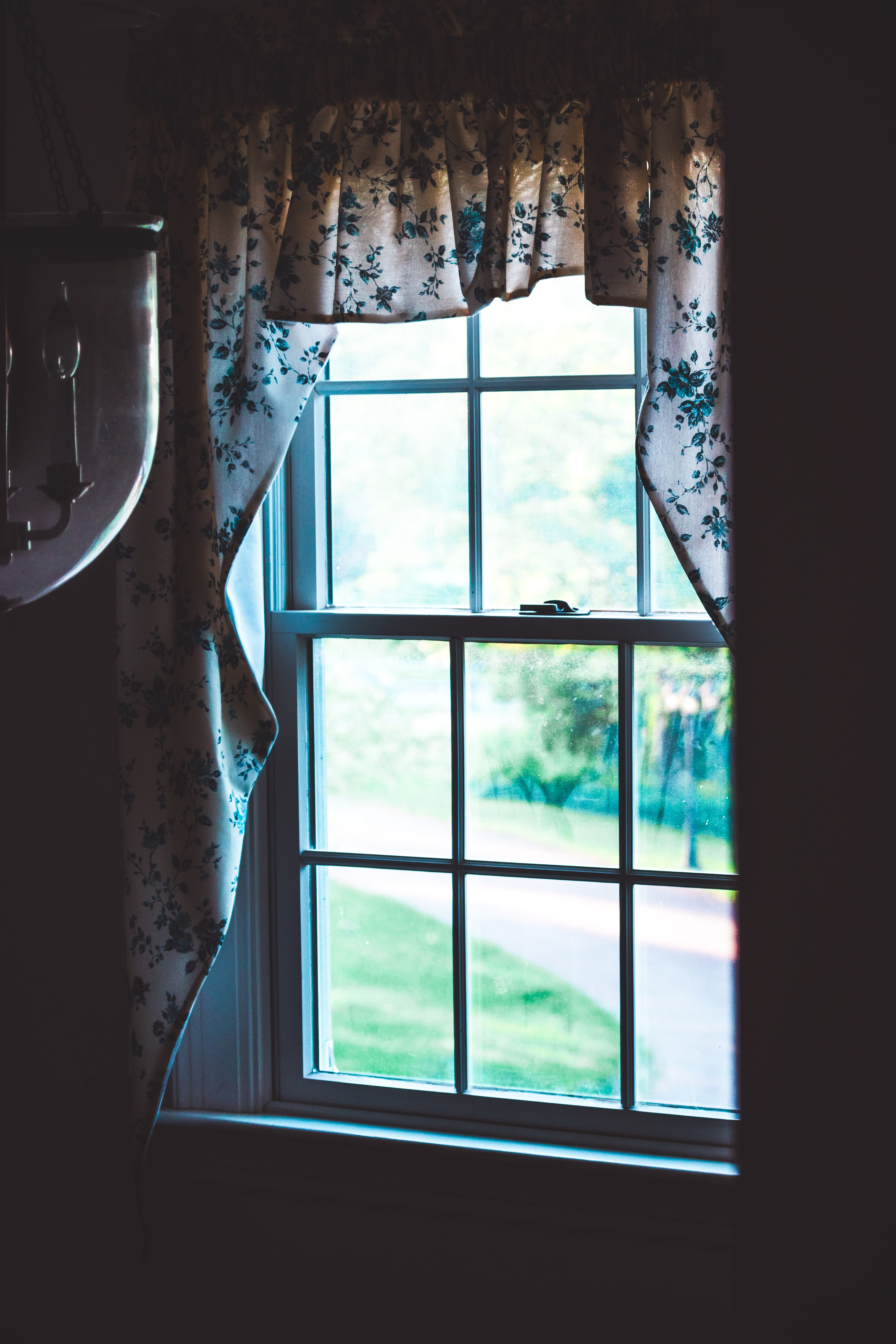 glass sash window with white floral curtain