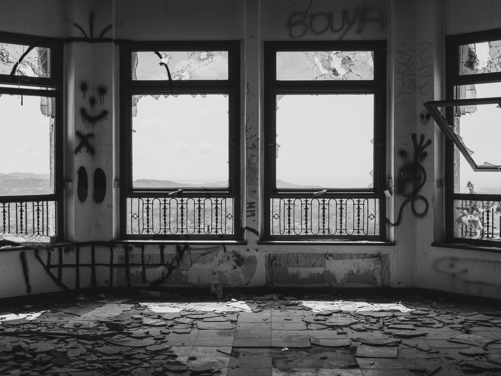 grayscaled photo of vandalized room