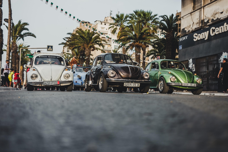 three Volskwagen Beetles on concrete road