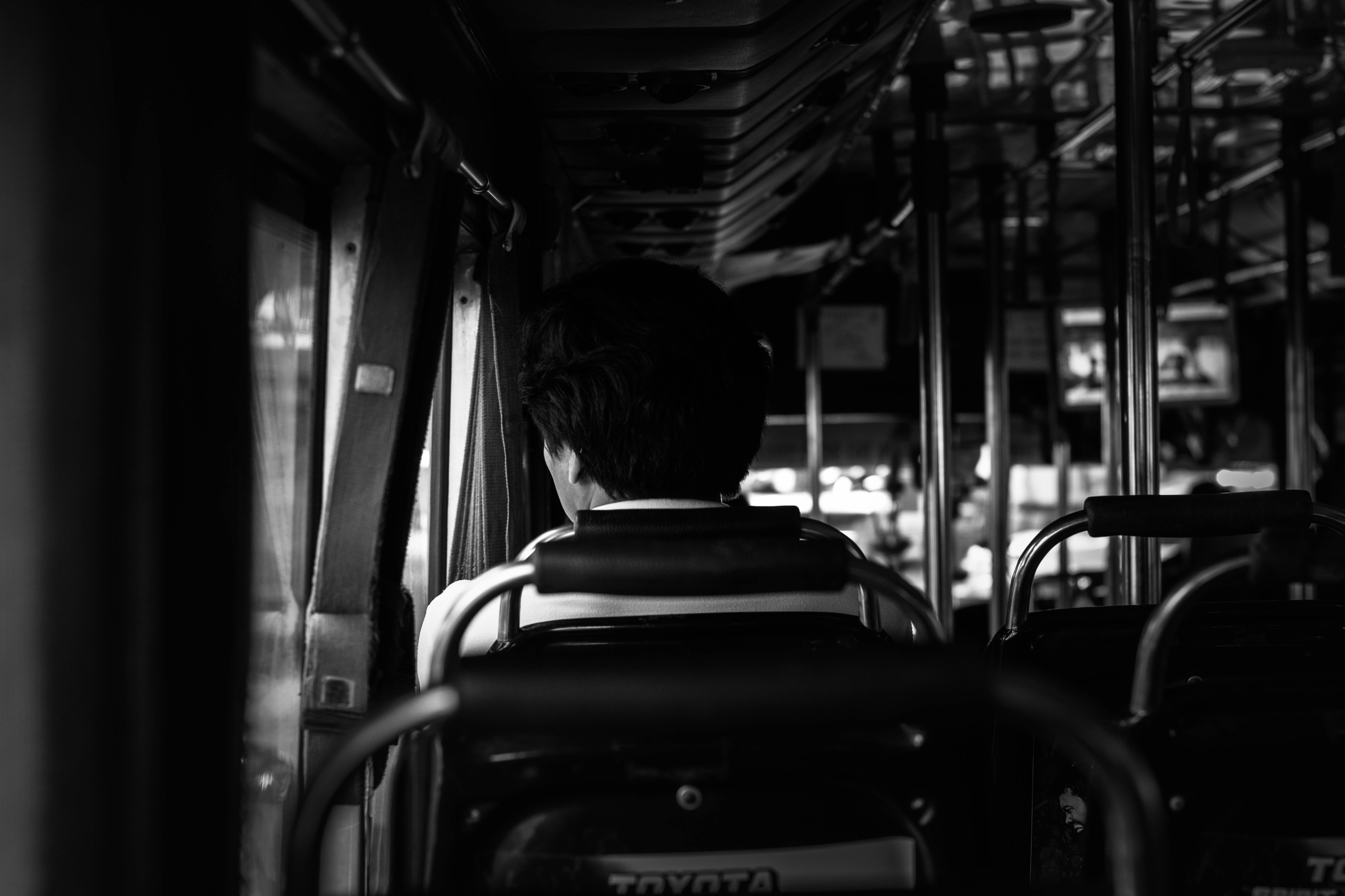 grayscale photography of of person sitting on car interior