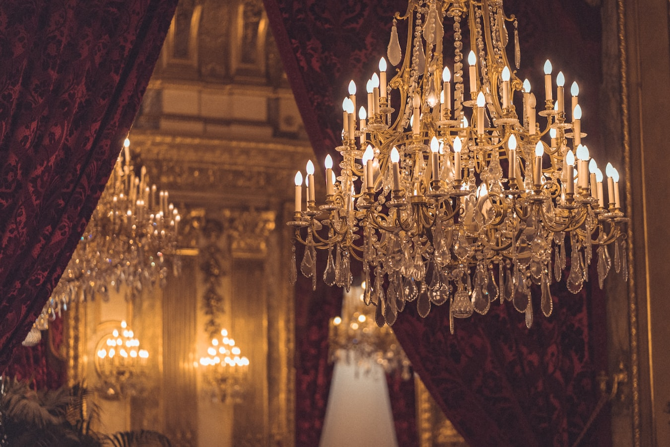 Gold and crystal chandelier in front of a mirror and some red velvet curtains.