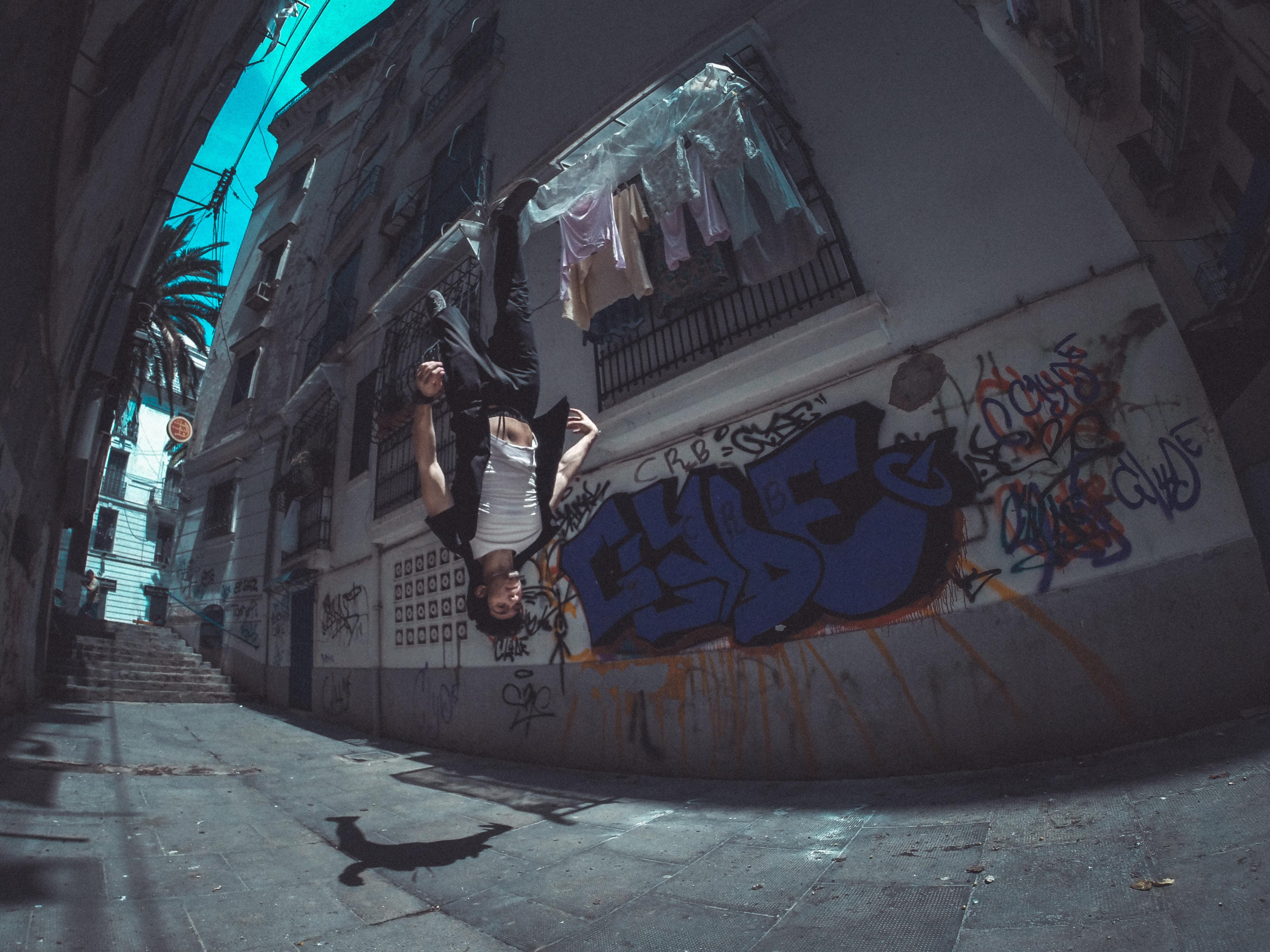 man performing backflip between house