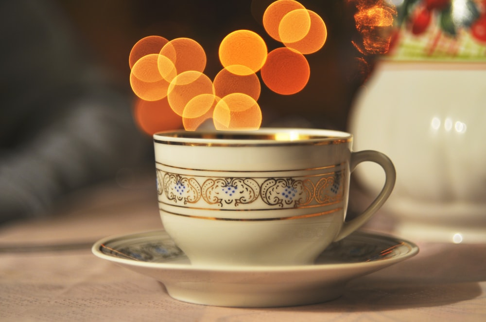 white and brown ceramic teacup on table