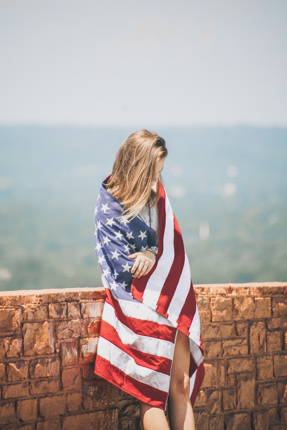 woman standing leaning on brick wall wrapping body with U.S. flag near body of water
