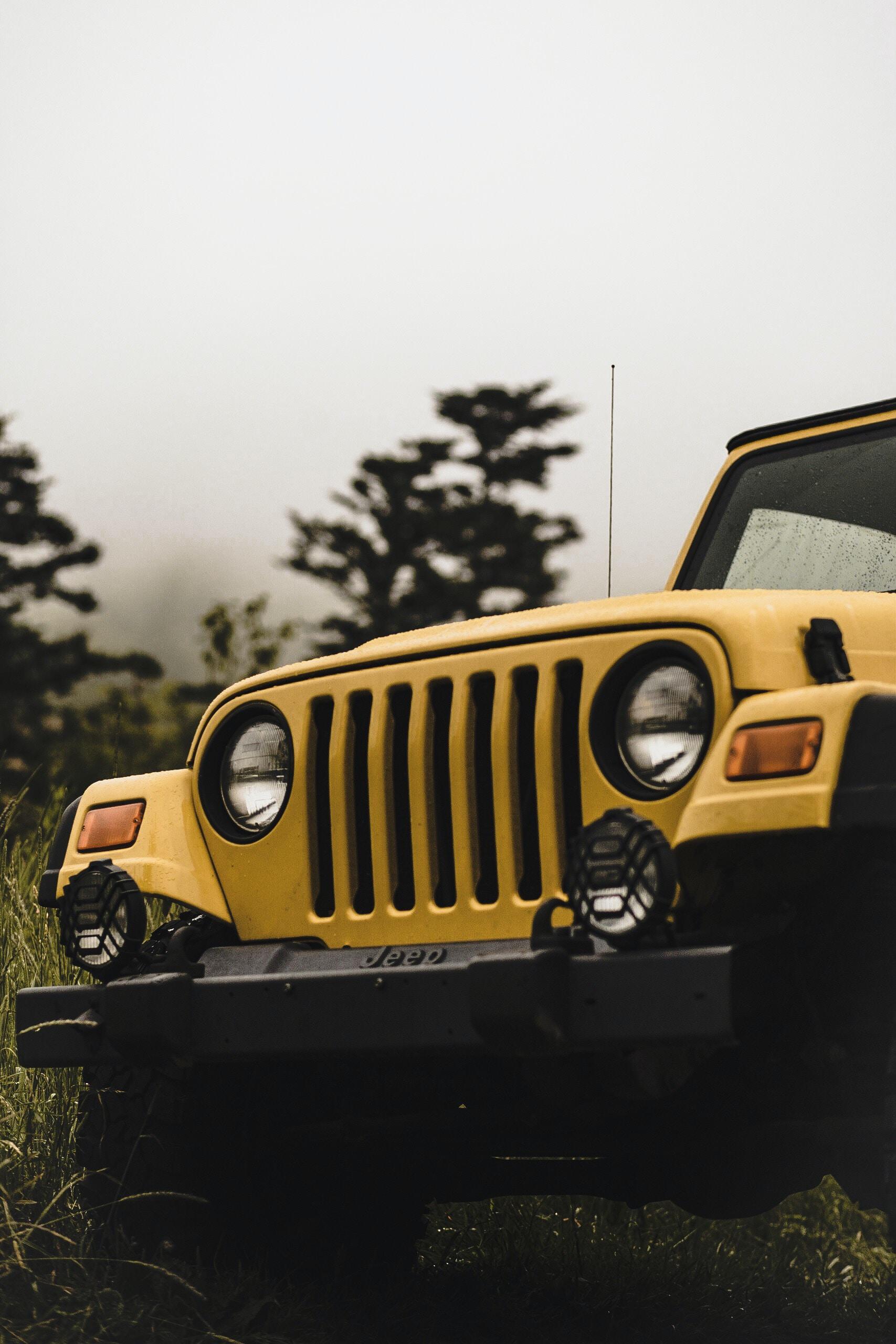 selective focus photography of yellow Jeep Wrangler SUV