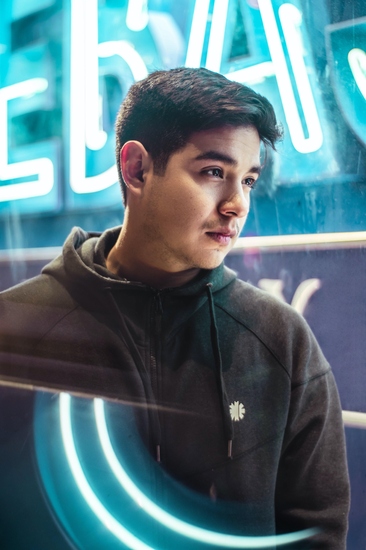 man wearing black zip-up hoodie standing near neon sign