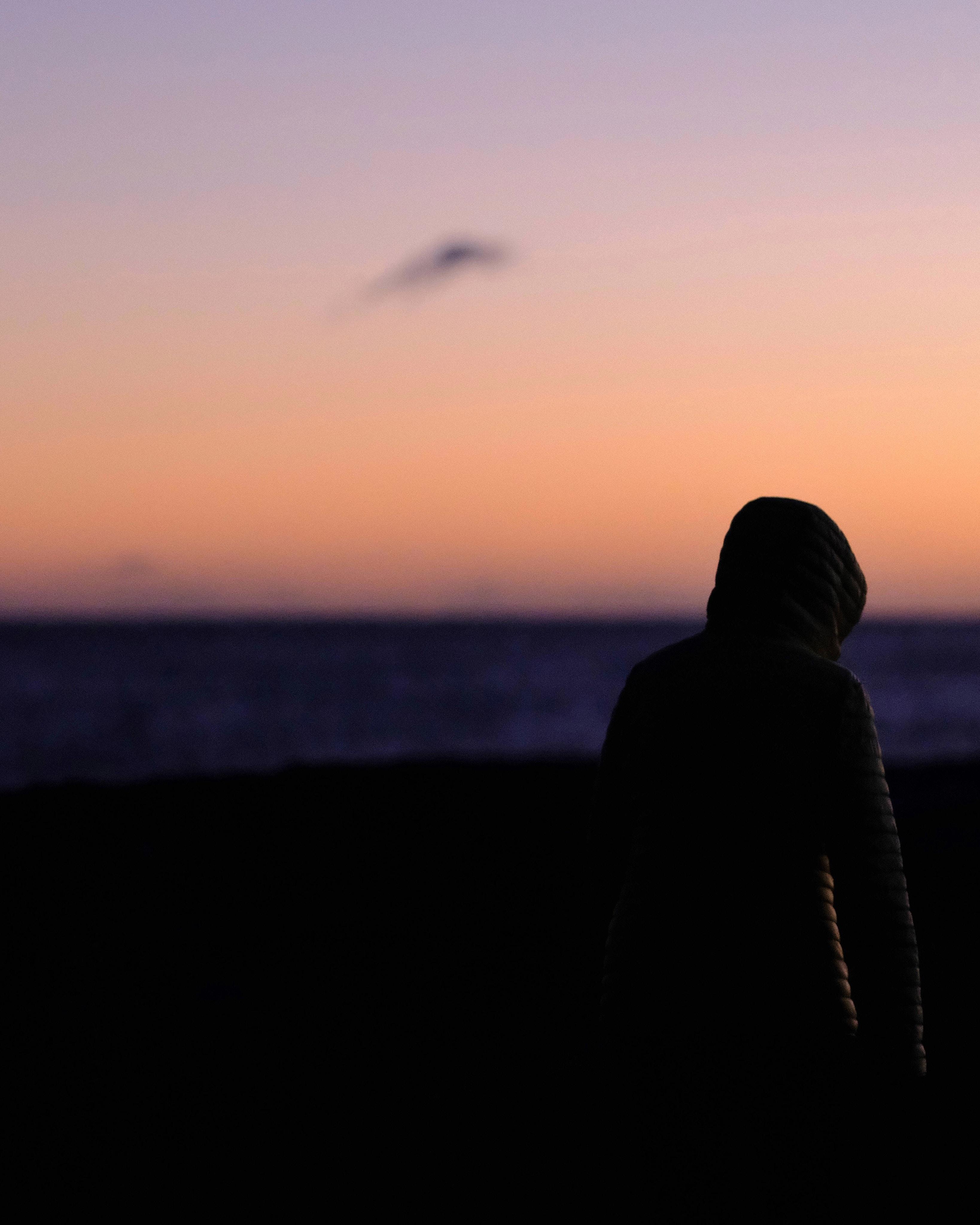 person wearing hoodie walking near shore