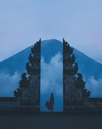 woman in between on concrete landmarks near white clouds