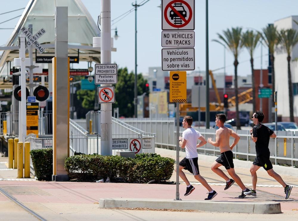 three men running beside signage