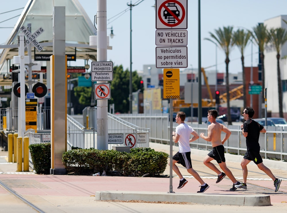 three men running beside signage
