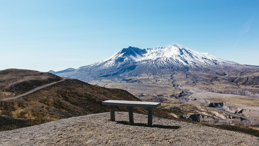 bench on gray ground near mountains