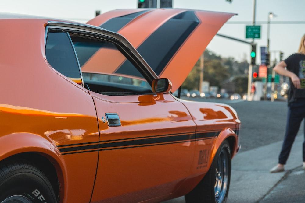 orange and black car parked on roadside