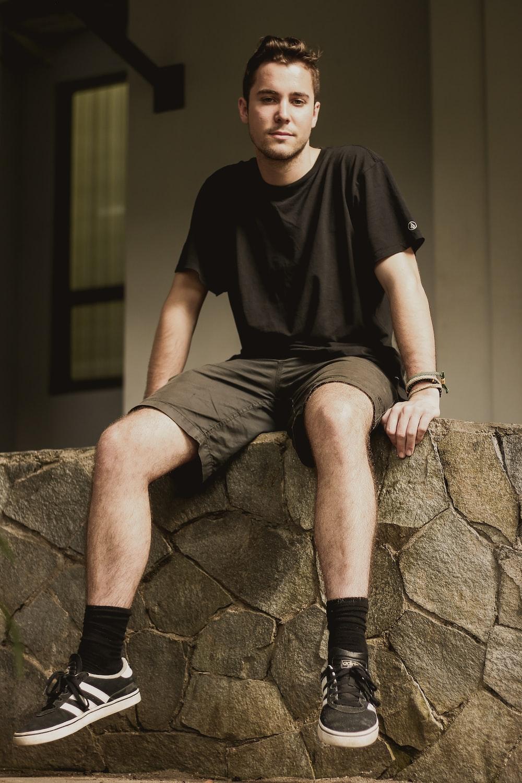 man wearing black crew-neck shirt sitting on concrete floor
