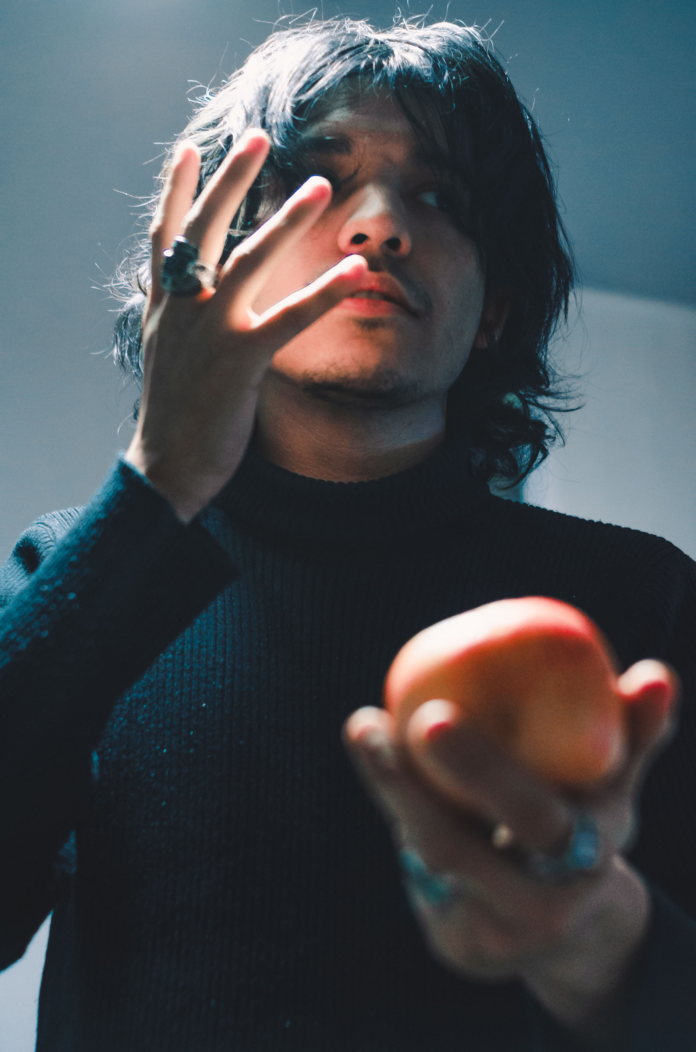 man holding apple fruit while raising his right hand