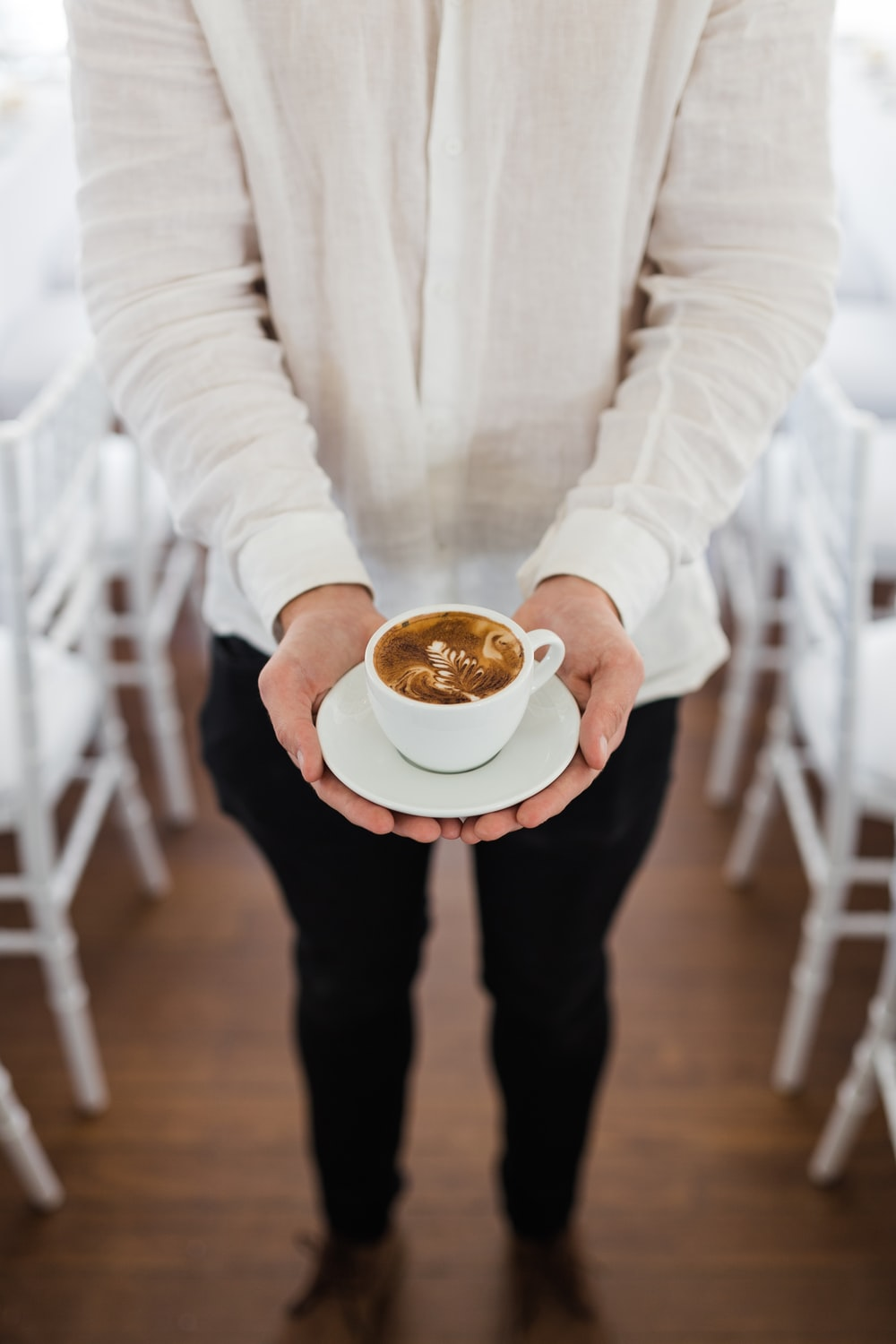 person holding coffee near dining tables