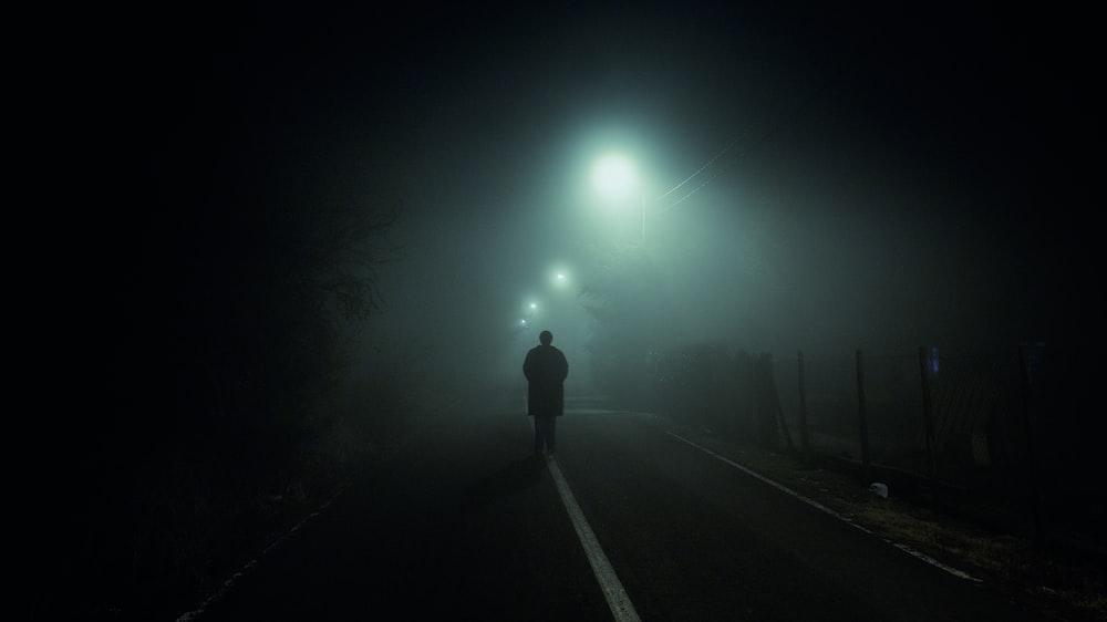 man walking at blacktop road with turned on streetlights