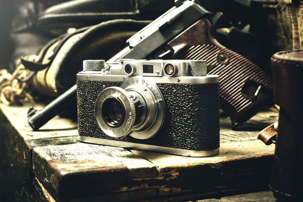 close-up photo of gray and black bridge camera and pistol