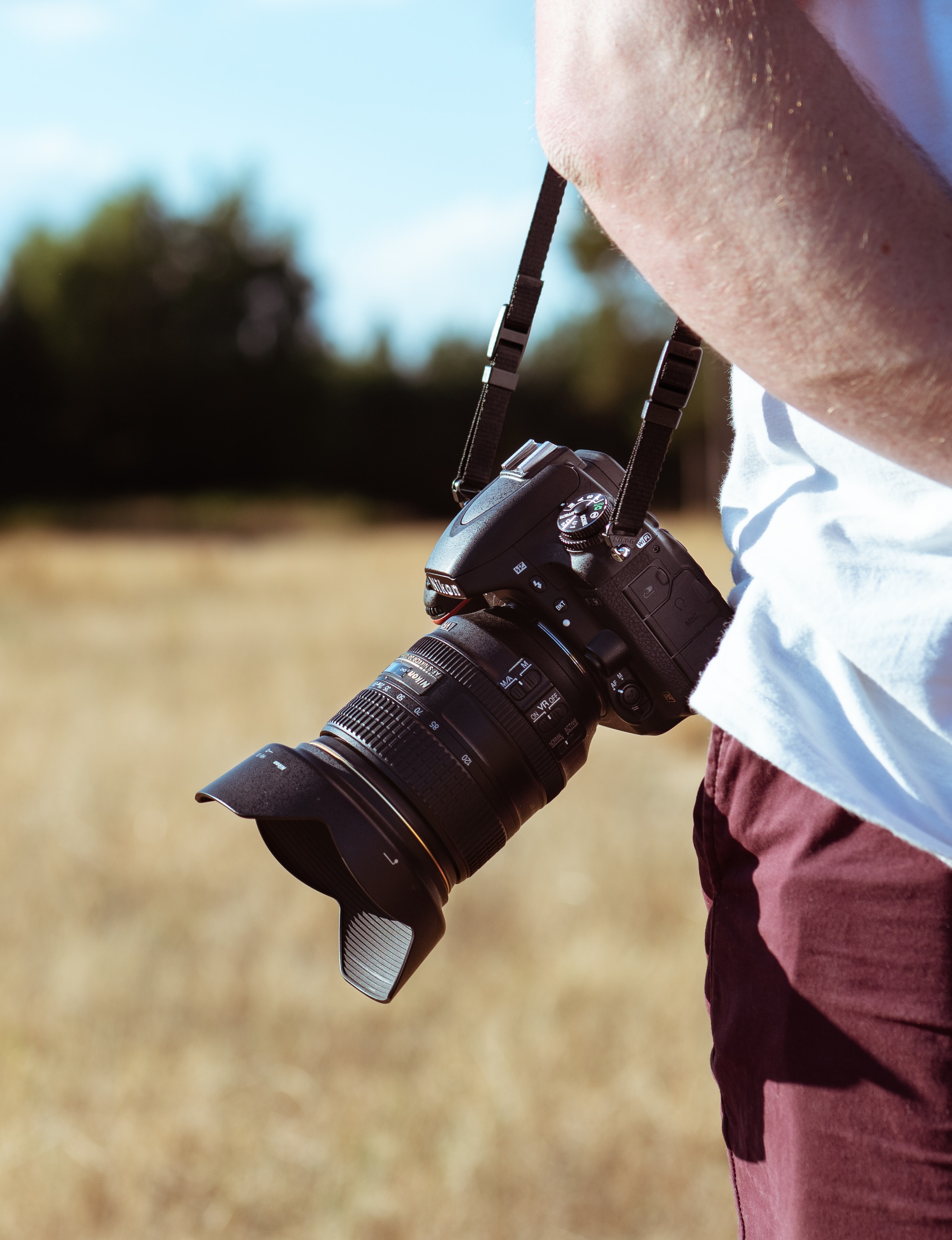 person holding camera standing on grass