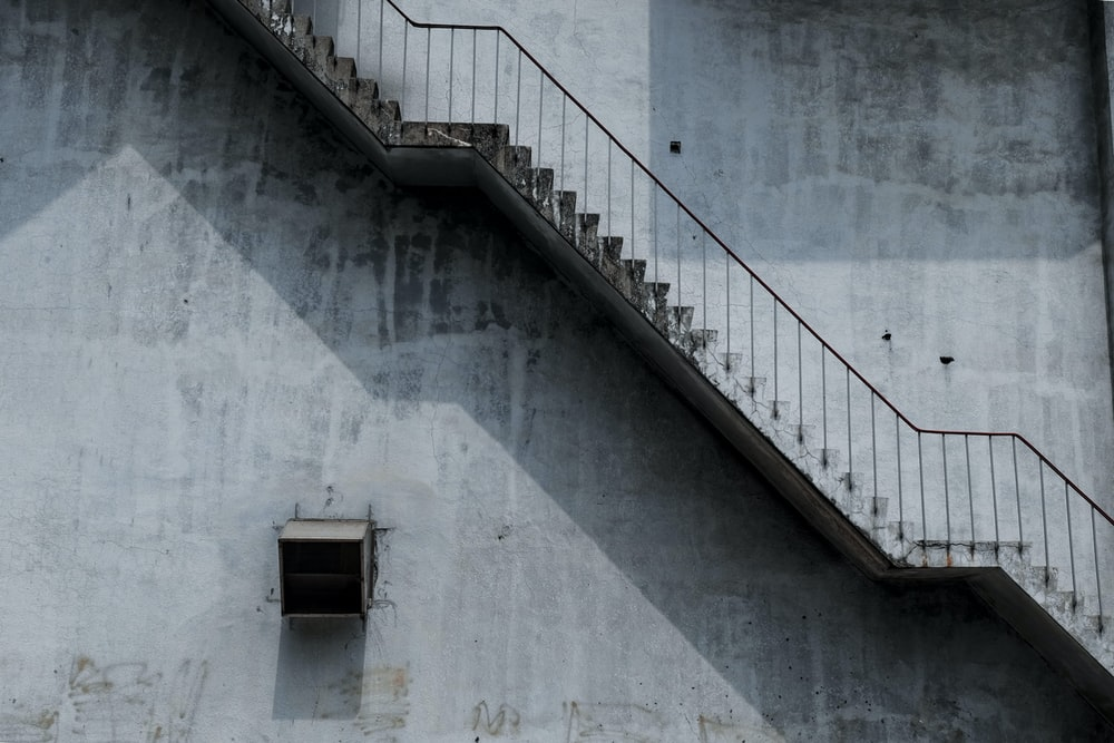white concrete stairs beside building