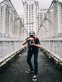man holding camera on pathway