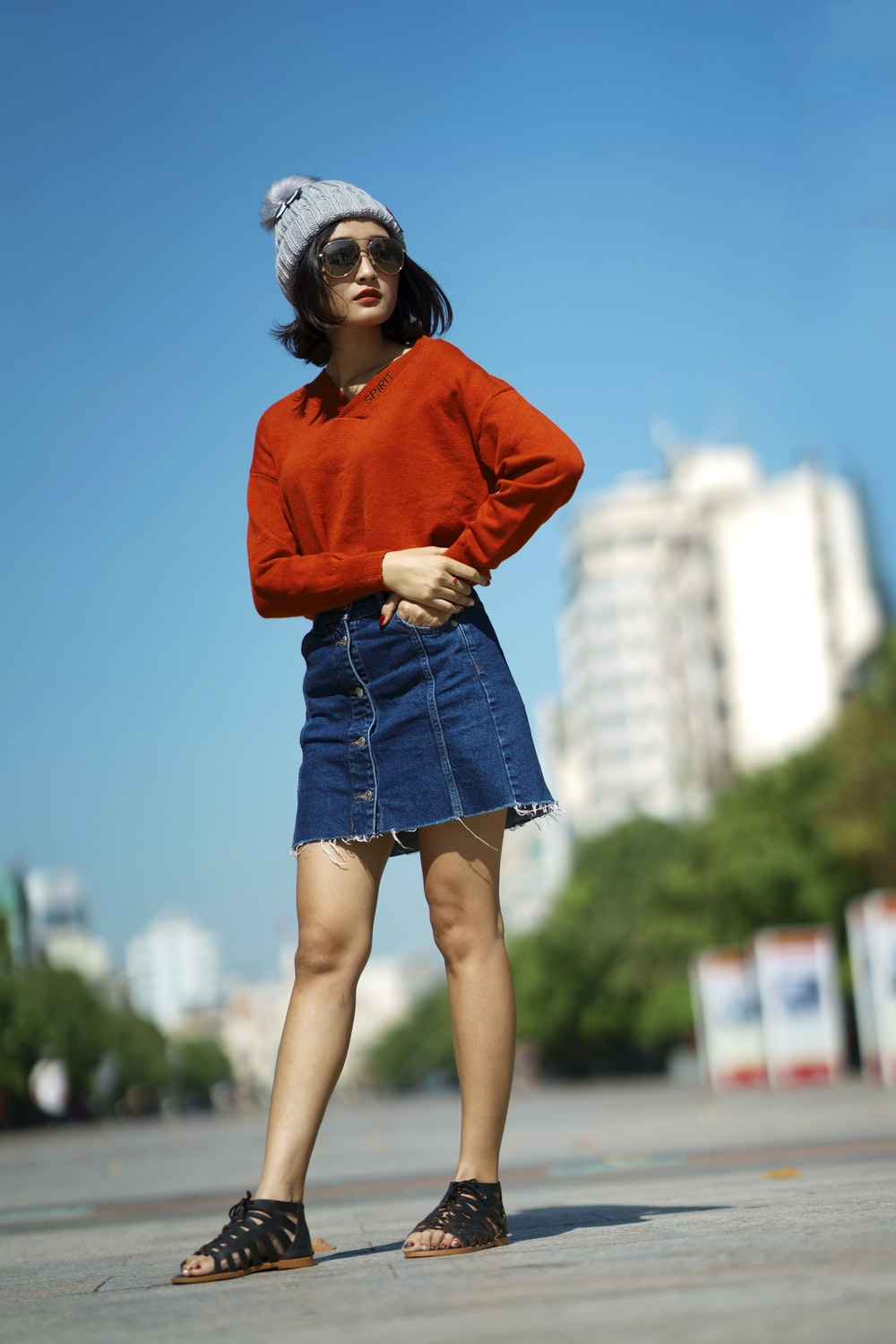 selective focus of woman wearing red long-sleeved shirt and blue denim skirt standing on road
