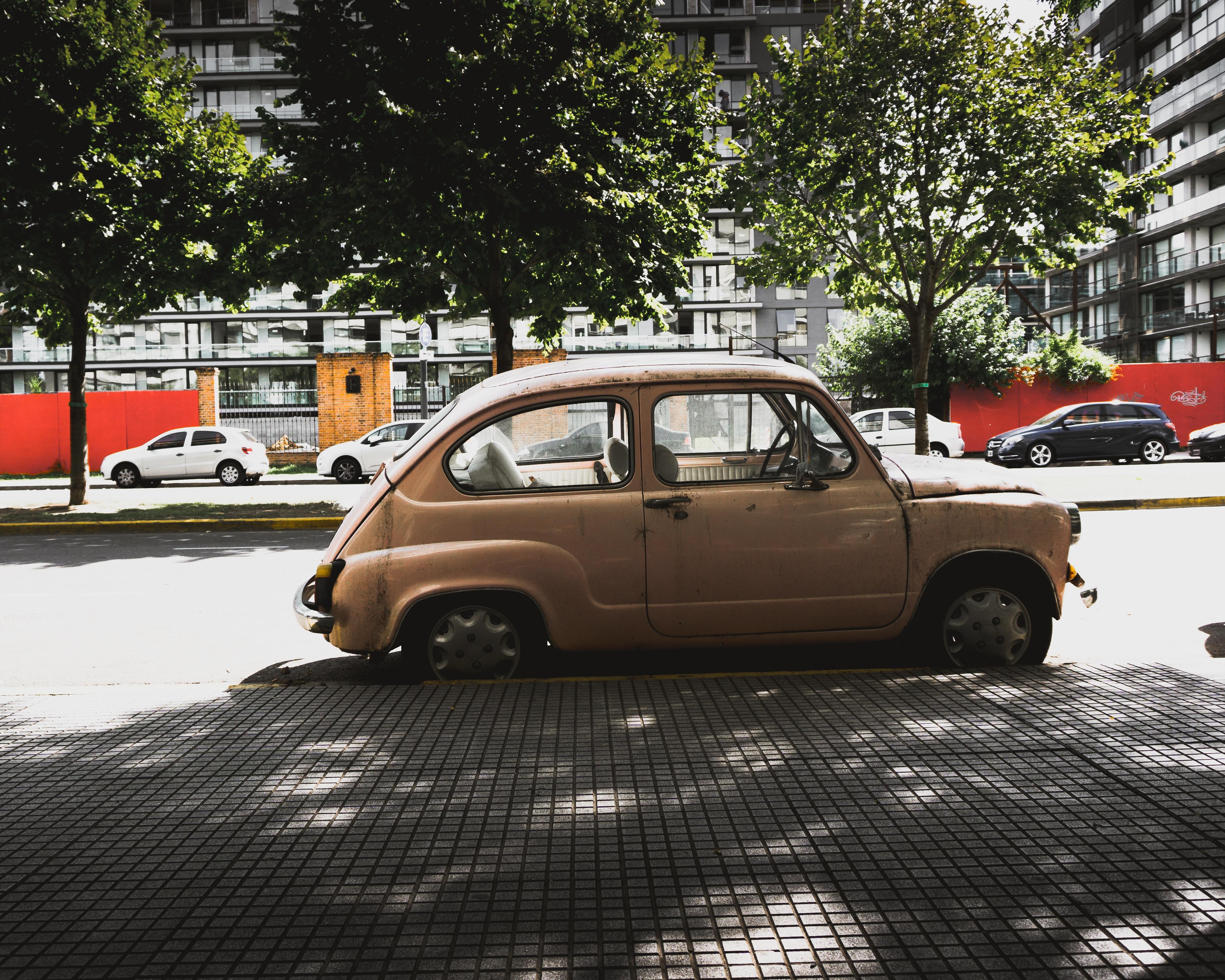 brown 3-door hatchback parked near road gutter