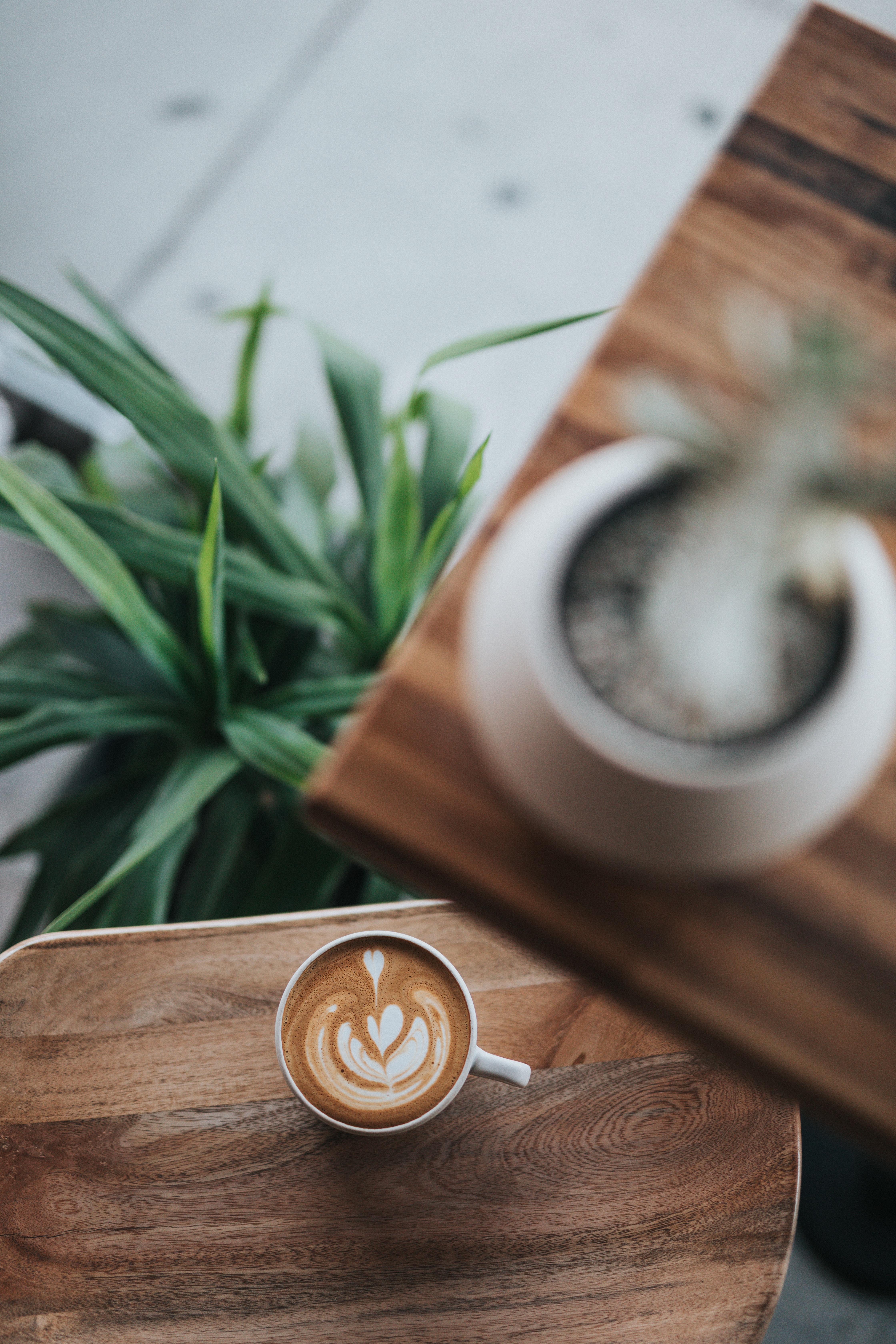 white ceramic teacup on brown wooden desk