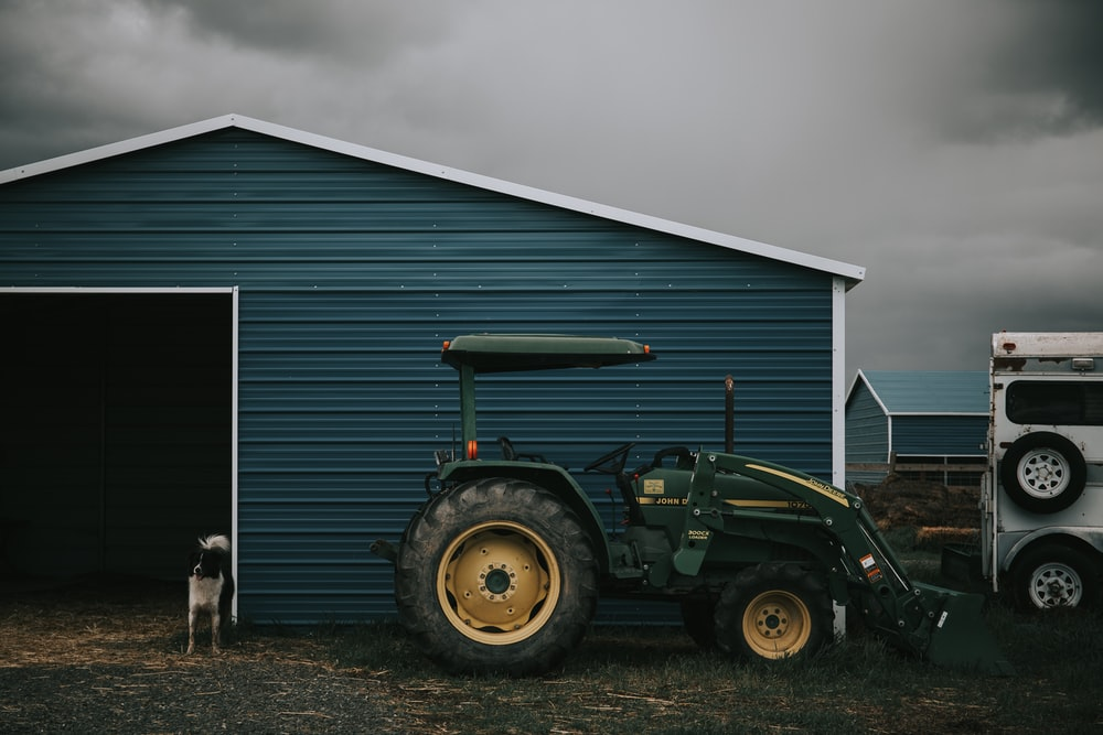 person taking photo of green tractor