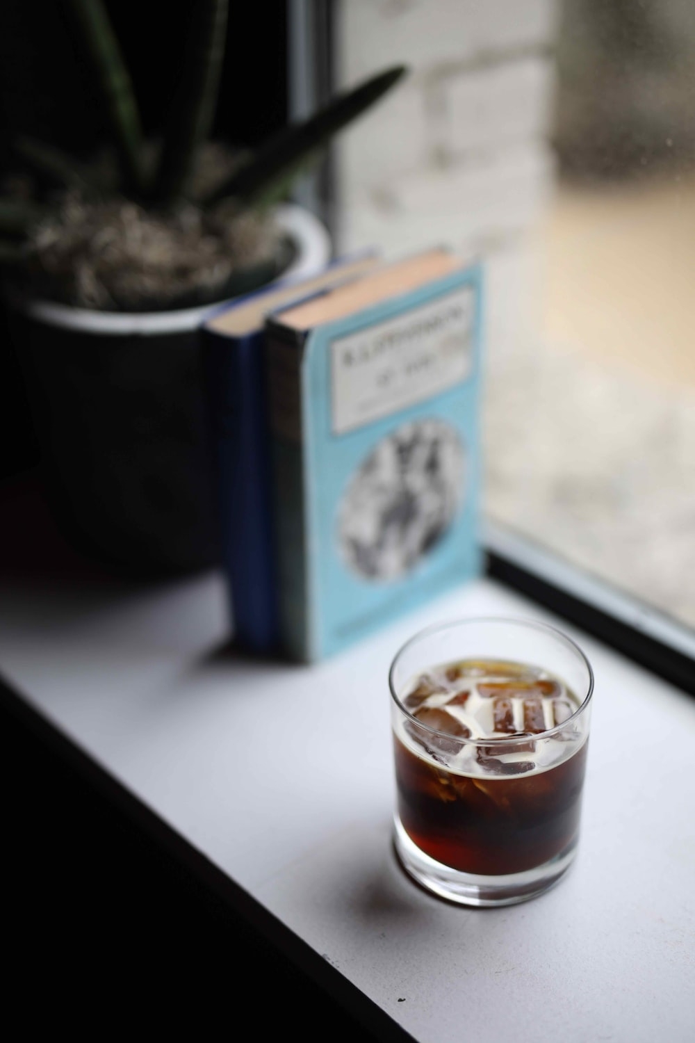 clear drinking glass beside book and plant