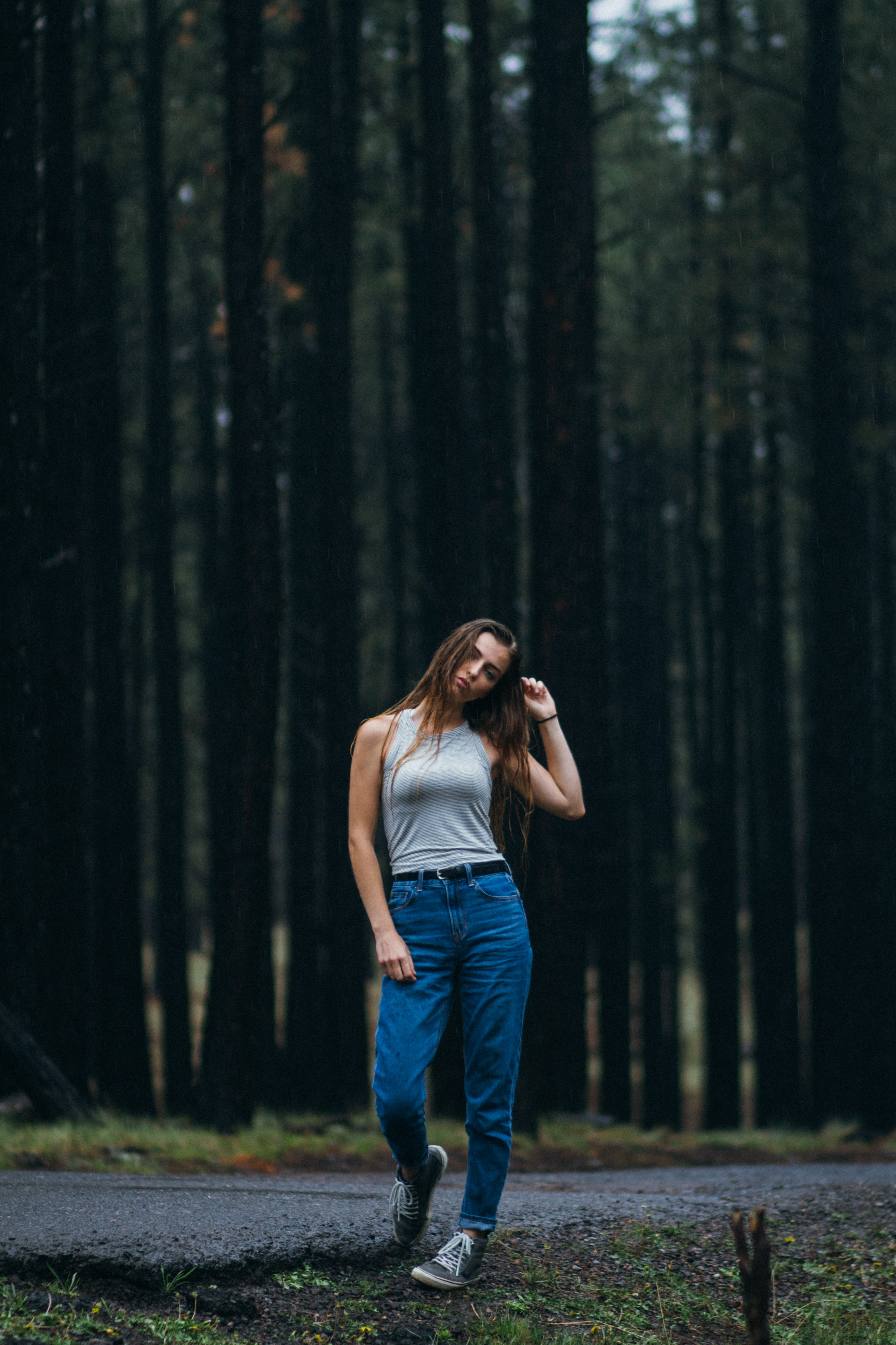 woman standing on walkway in front of forest trees