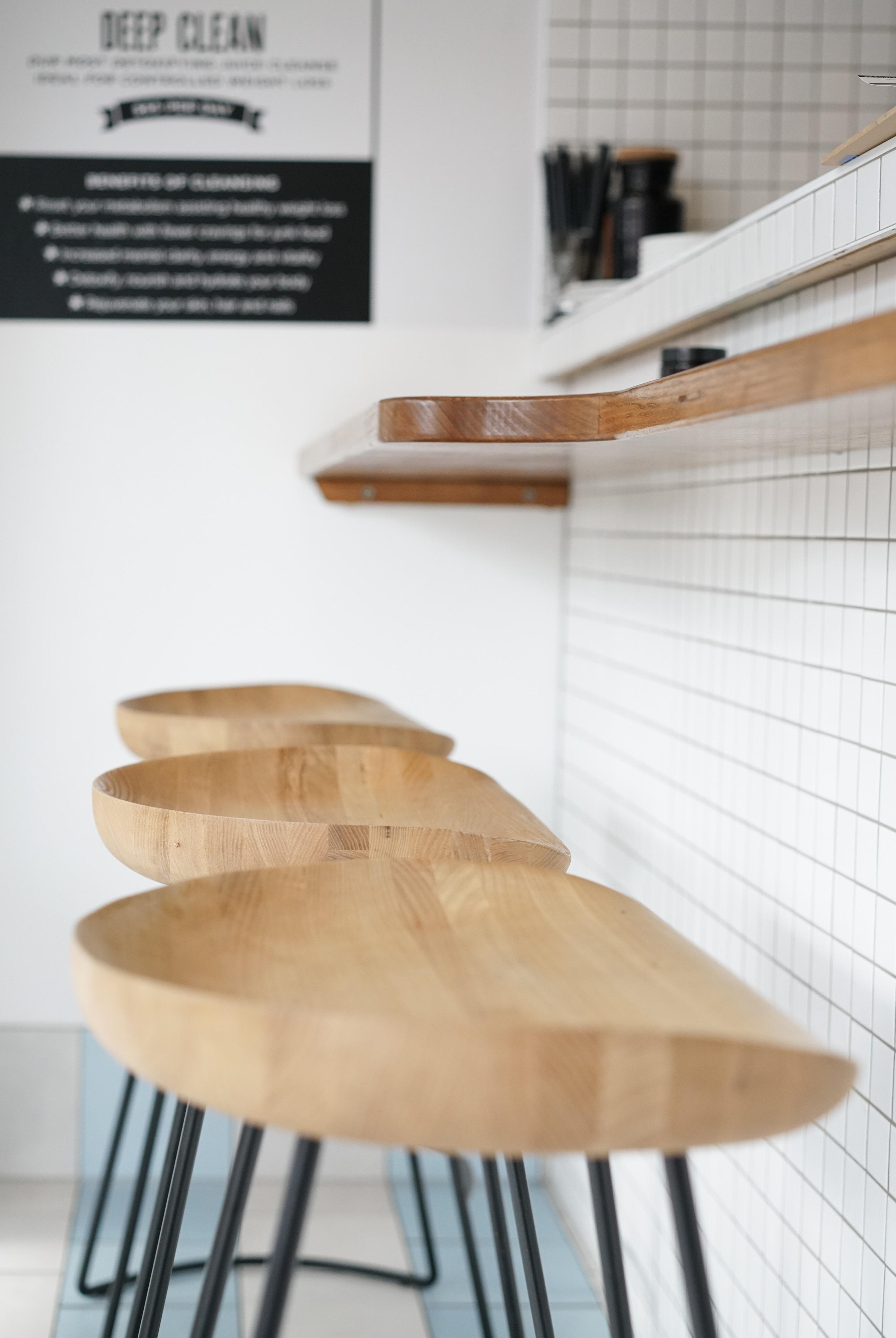 three brown wooden stools beside brown wooden desk