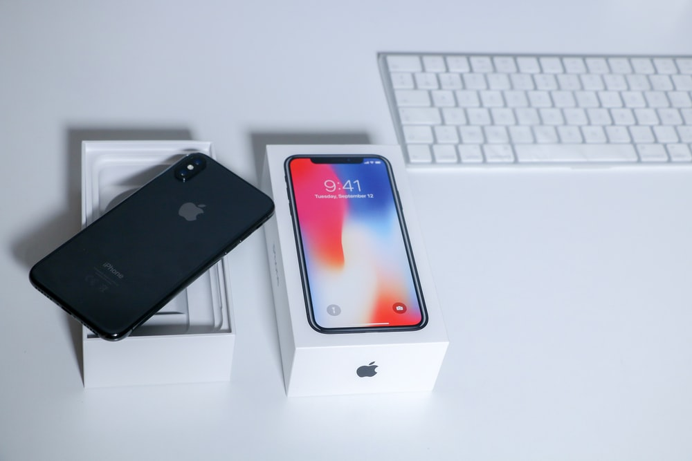 space gray iPhone X on table beside keyboard
