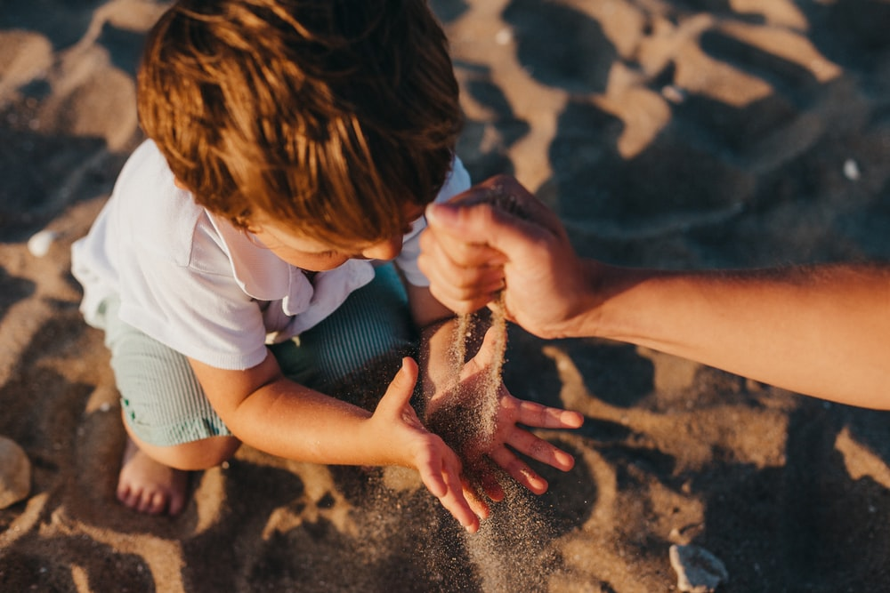 person pouring sand into boys hands