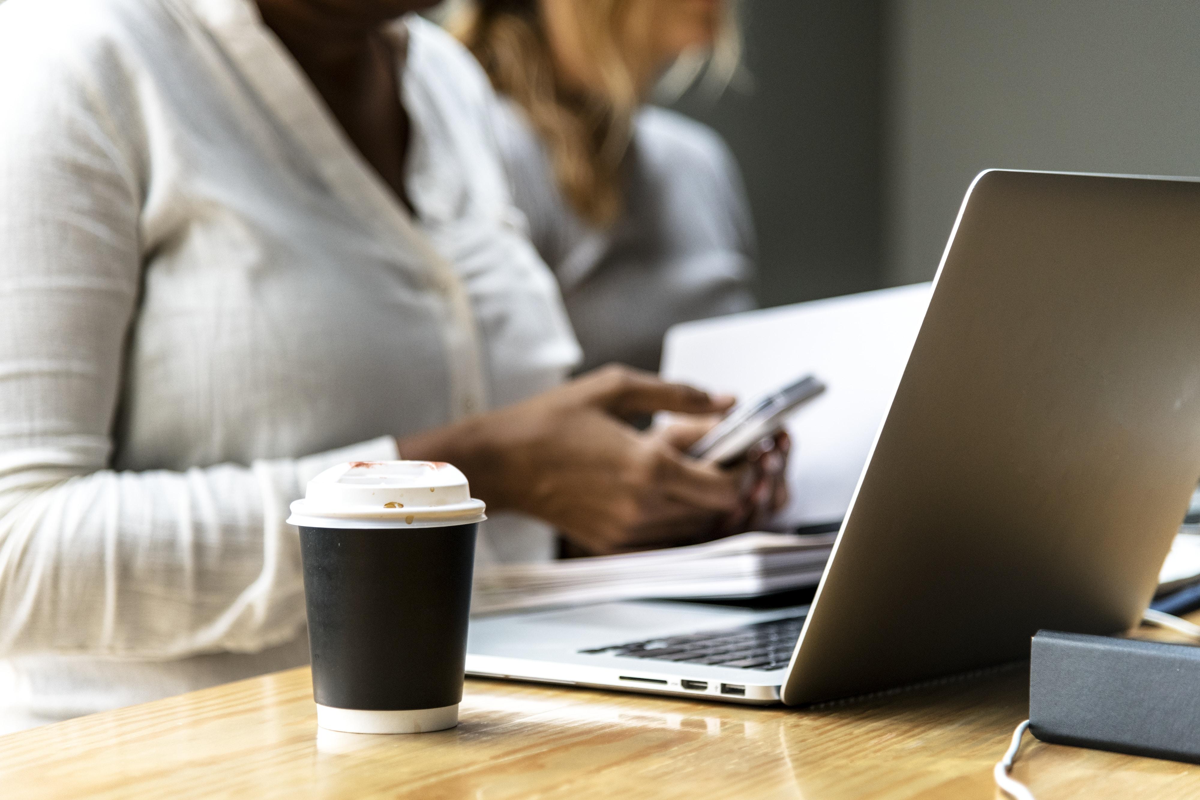 coffee cup beside laptop