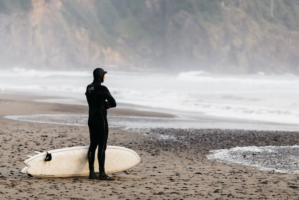 man standing on shoreline with surfboard