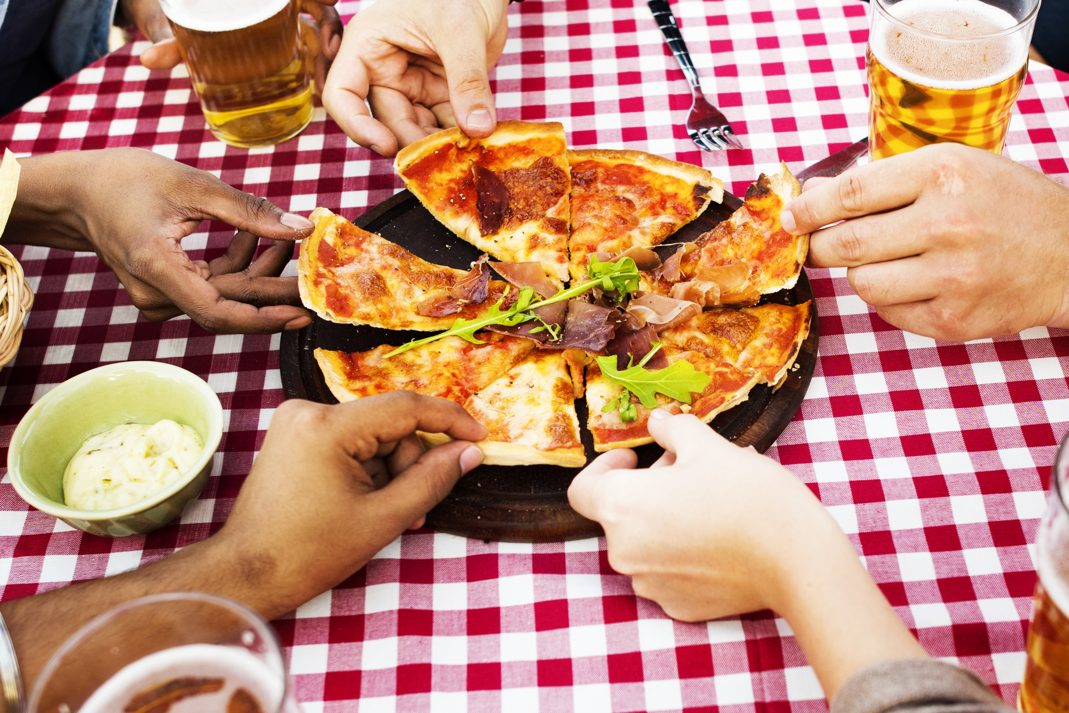 people holding slices of pizza
