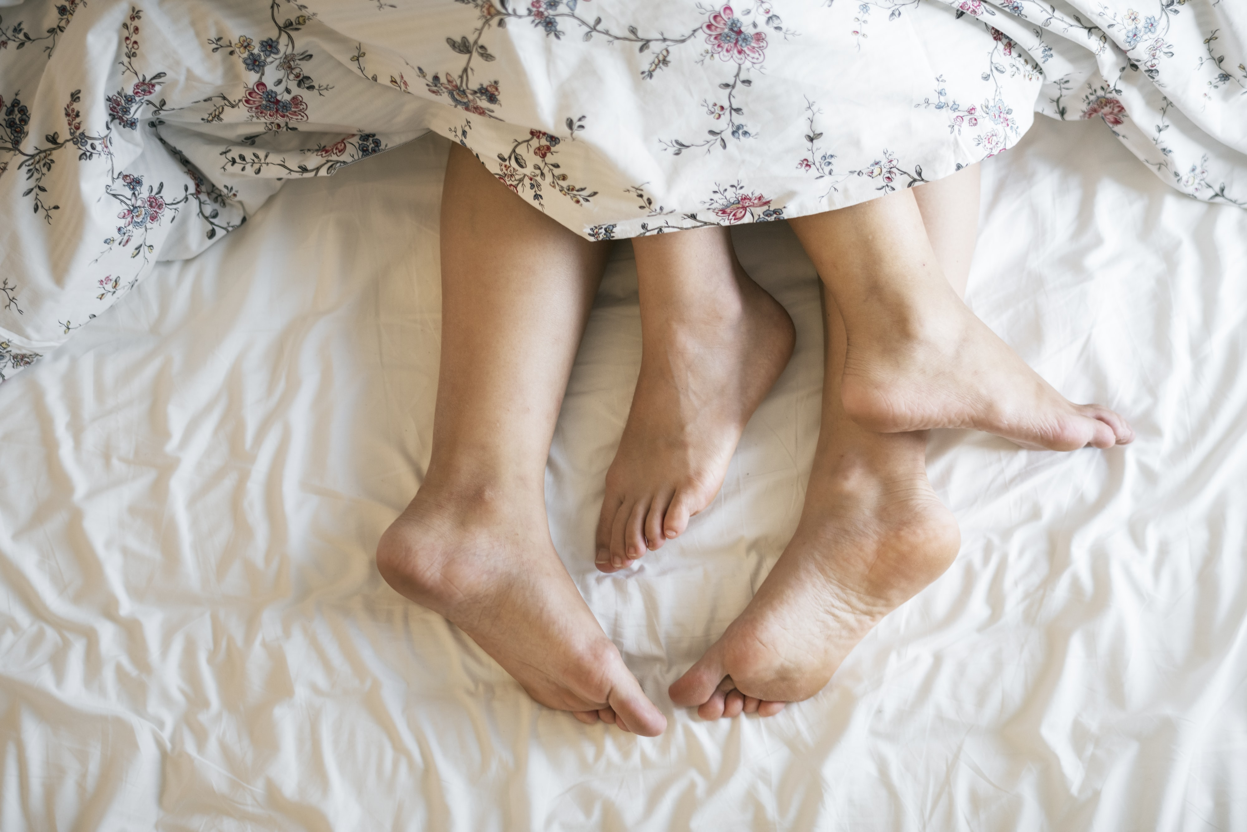 feet of two people on bed