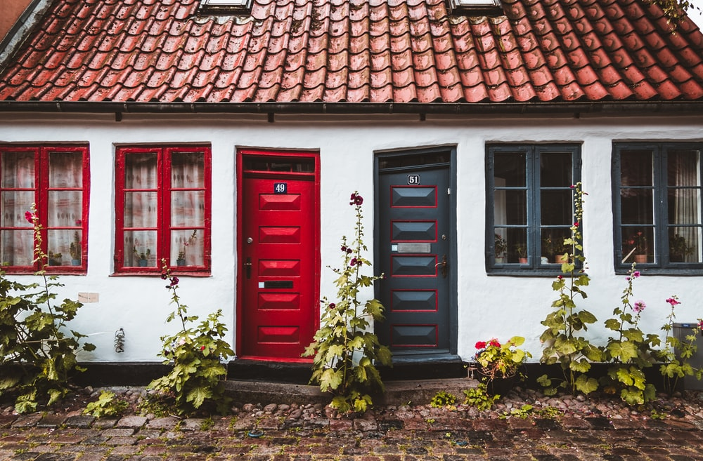 two red and black house door with plants