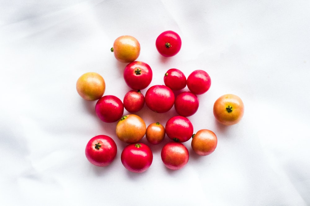 photo of red and brown cherries on white surface